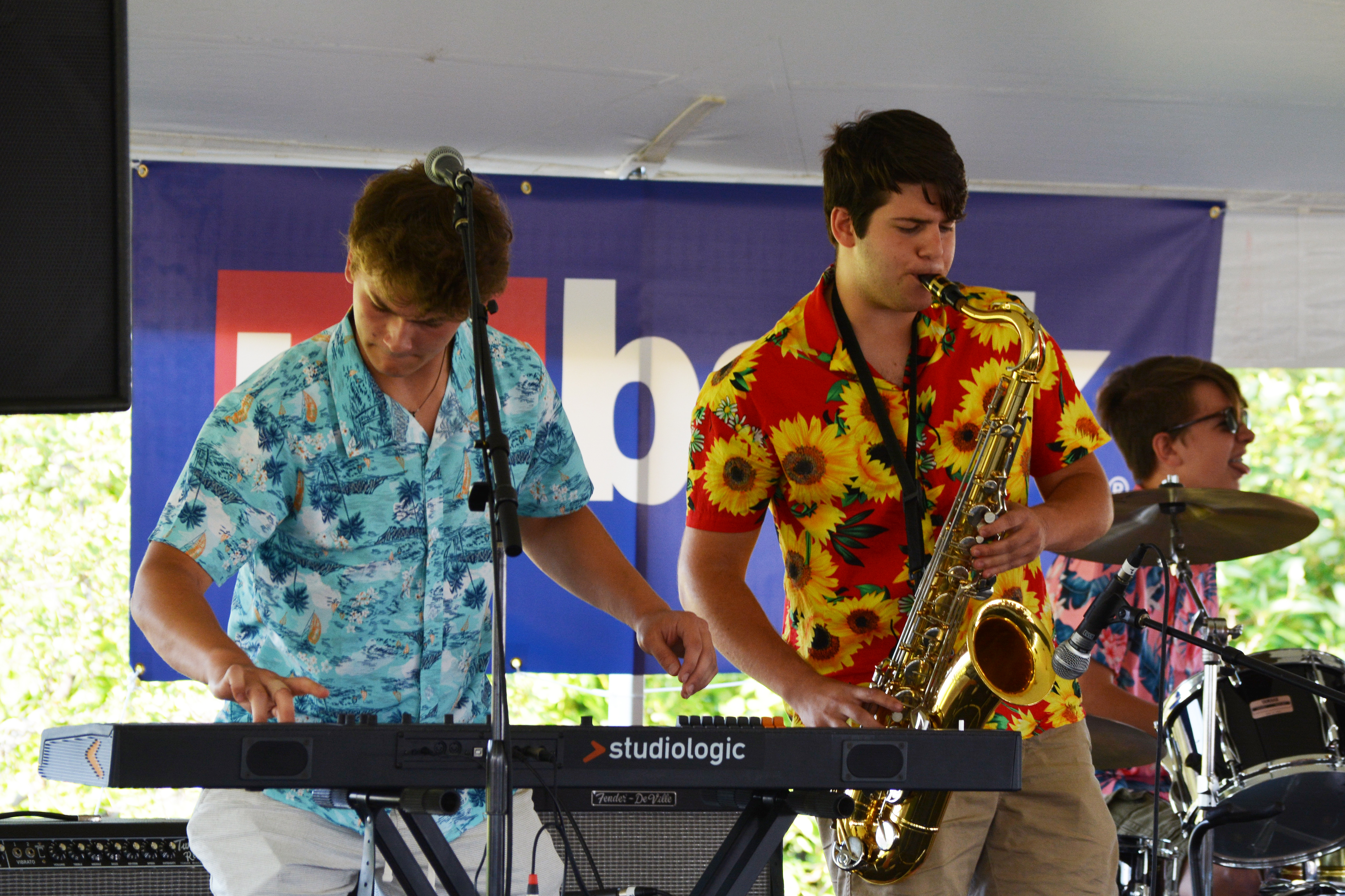 Musicians play keyboard and saxophone onstage