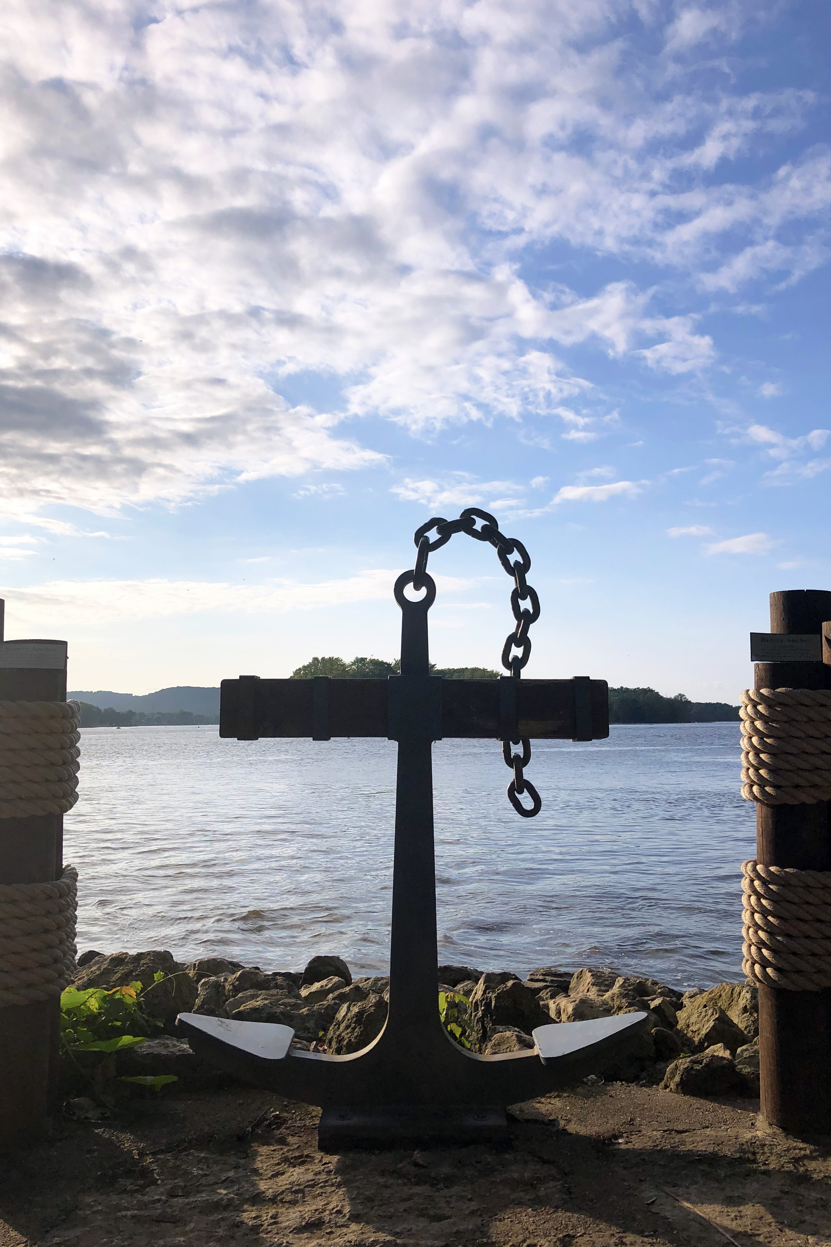 An Anchor between two wooden posts with the Mississippi River in the background
