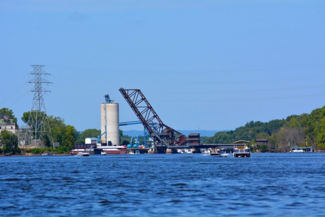 A railroad bridge rises to allow tall boats to pass underneath