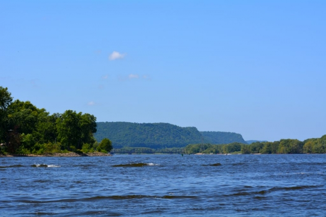 The view of bluffs in the distance shot from the river