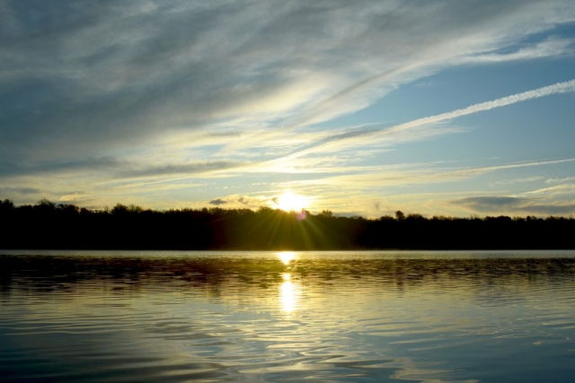 The sun rises above the trees across Tobyhanna Lake