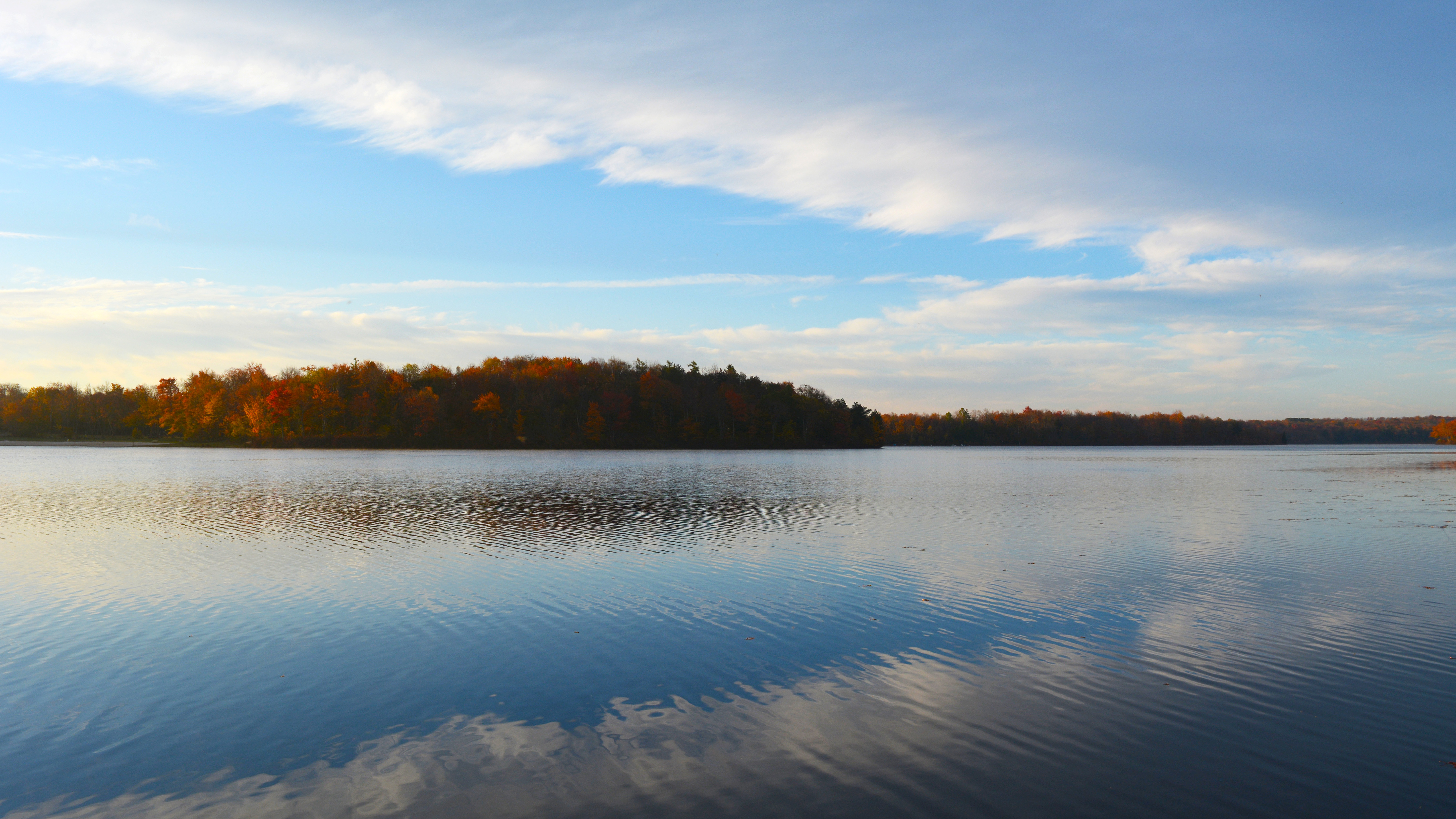 The view of colorful trees across Tobyhanna Lake at sunrise