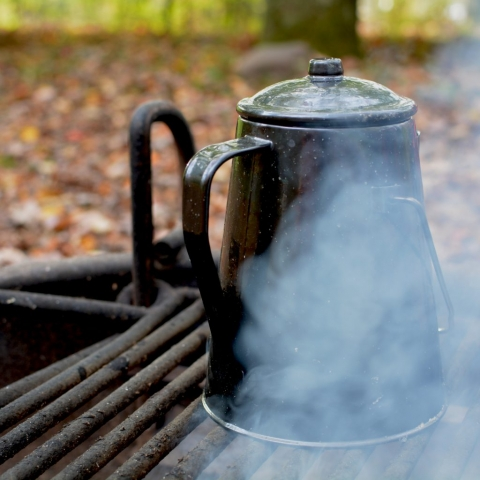 A kettle heating over an outdoor campfire