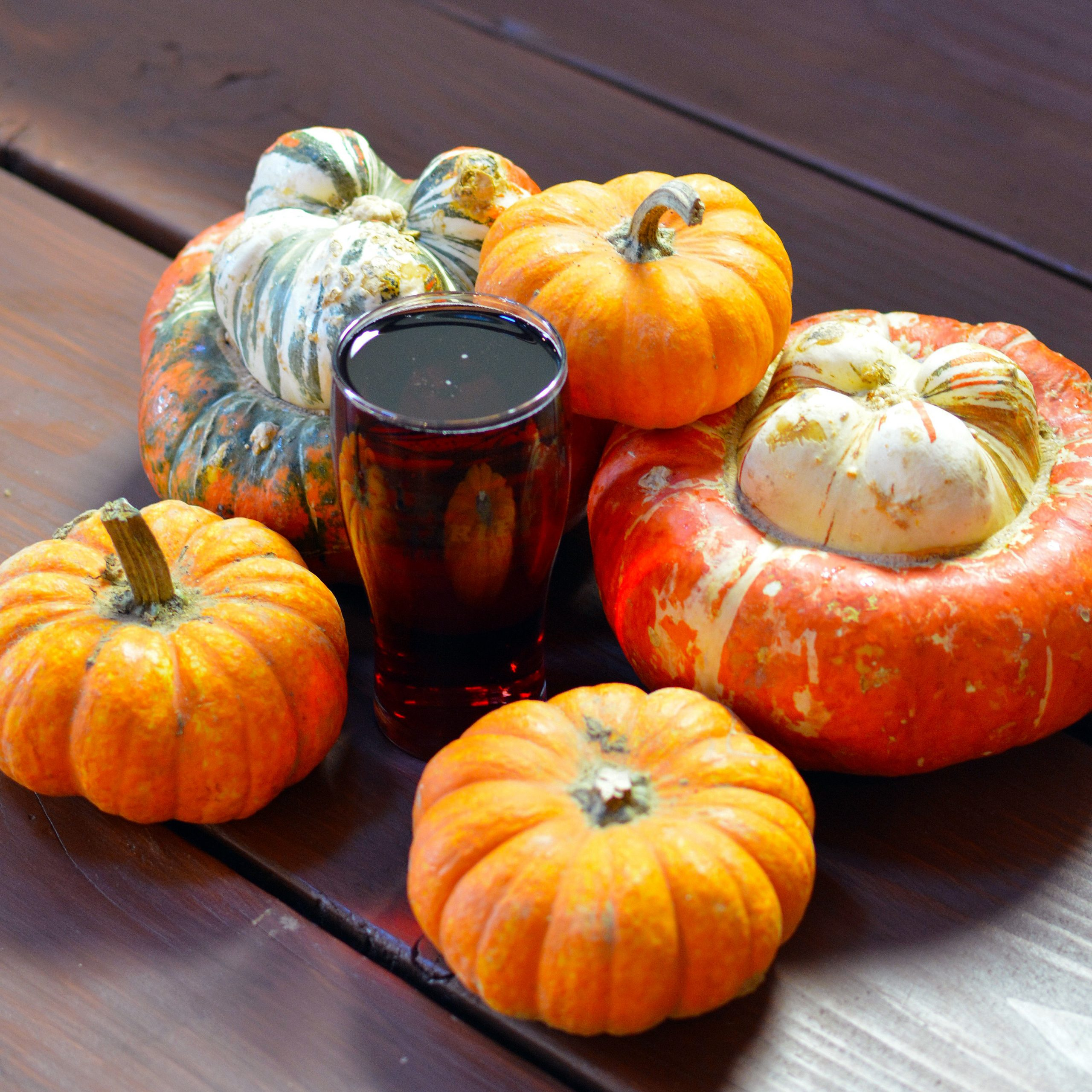Photo of a glass of Cranberry Cider surrounded by orange squashes and pumpkins