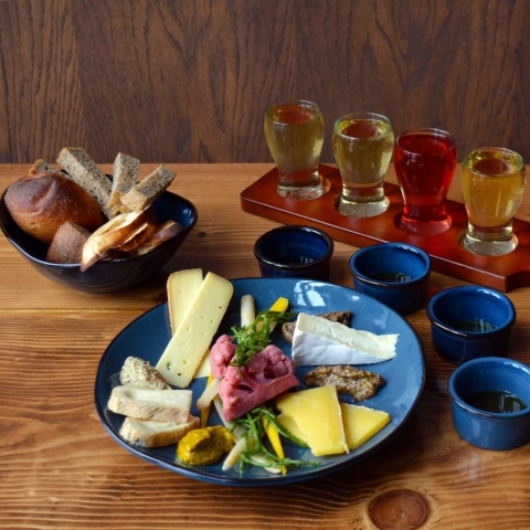 A charcuterie board with varieties of bread, cheese, honey, pickled vegetables, and artisanal mustards, with a flight of cider on the side
