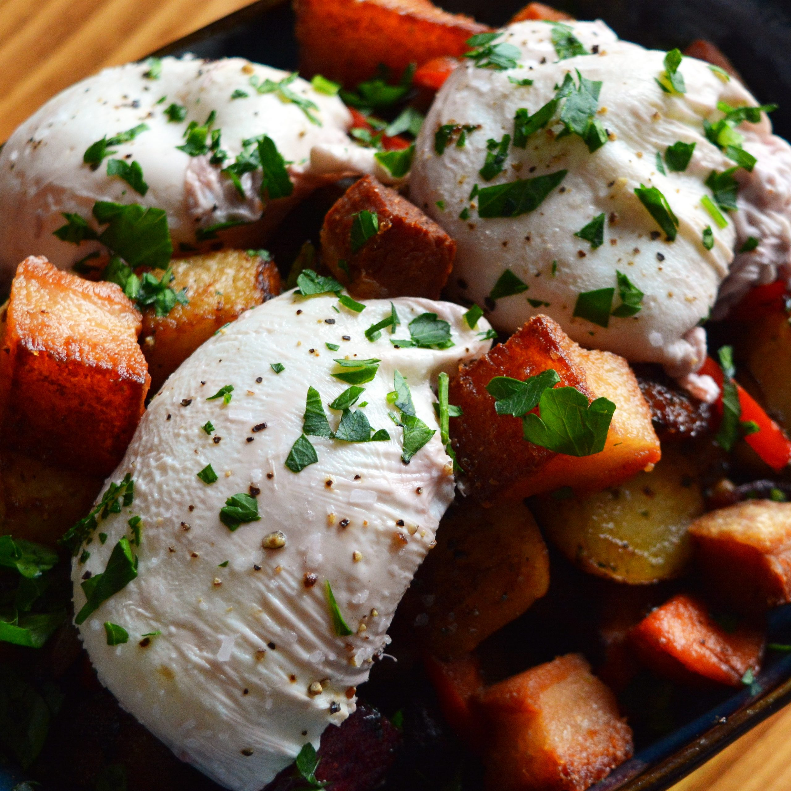 Three poached eggs over a bed of crispy, fried potatoes
