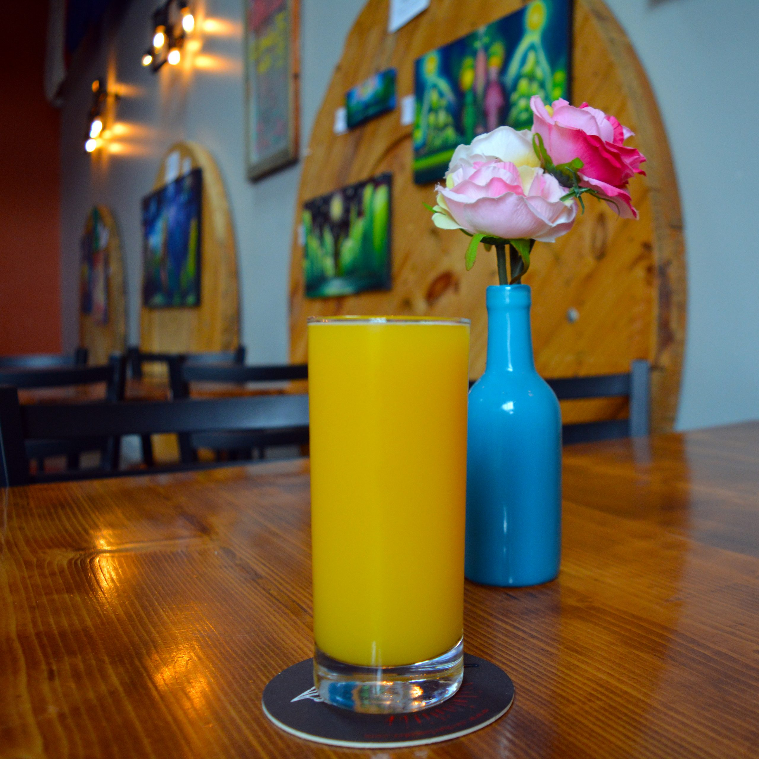 A photo of a mimosa with artwork and flowers in the background