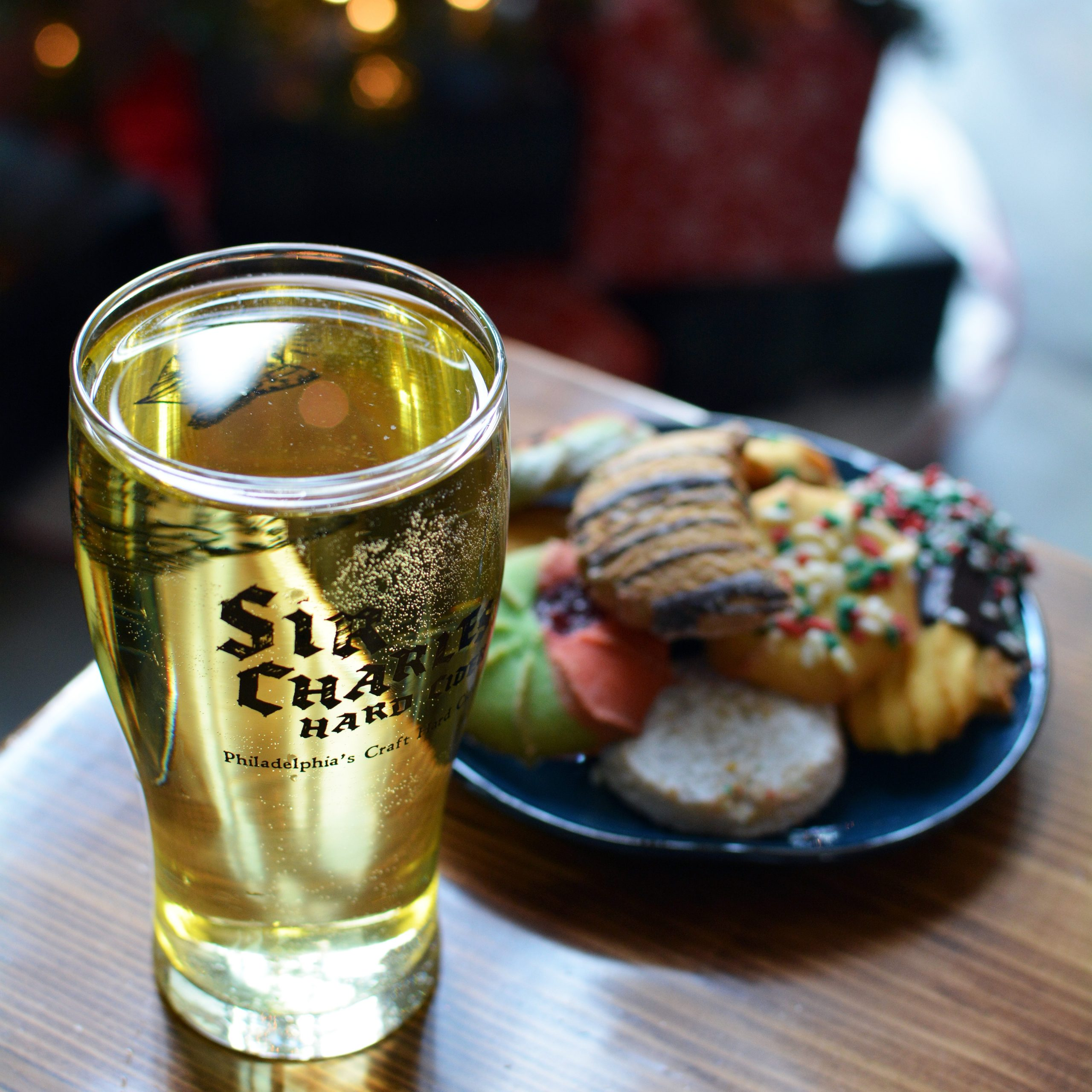 A glass of Sir Charles Hard Cider, with a plate of Christmas cookies in the background