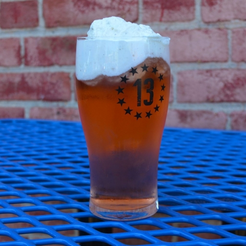 A photo of a red hard cider topped with whipped cream