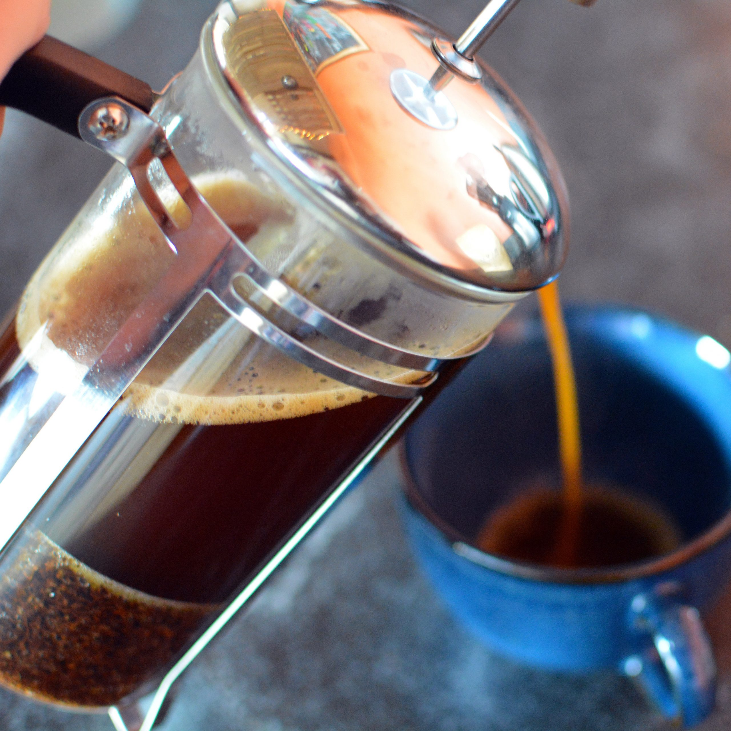 Coffee pours from a french press into a blue mug
