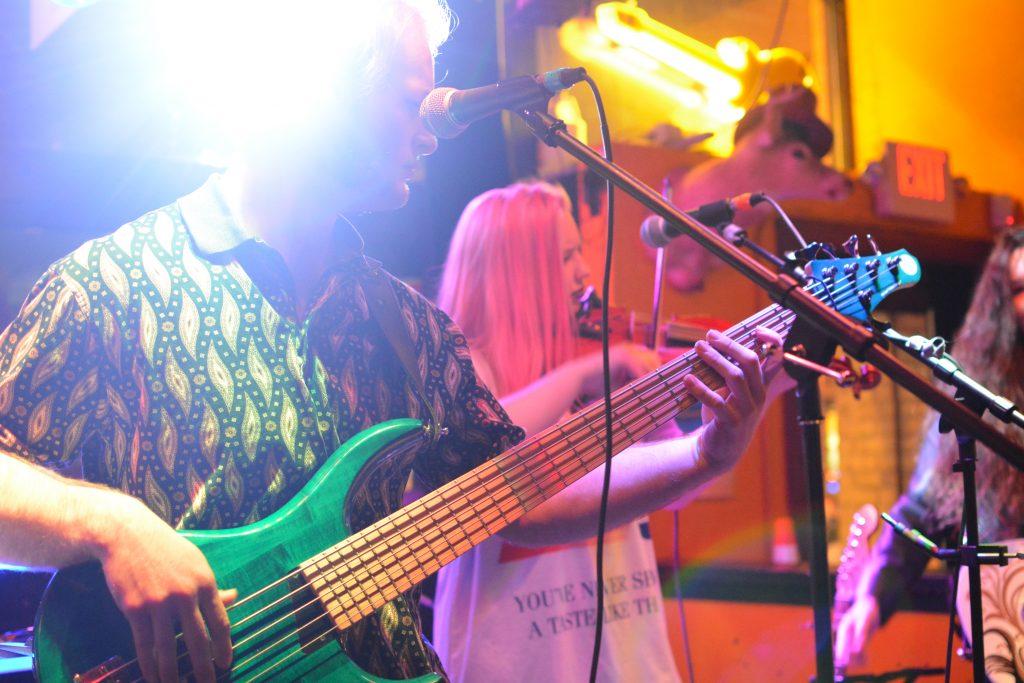 Saul Dinauer plays the bass guitar