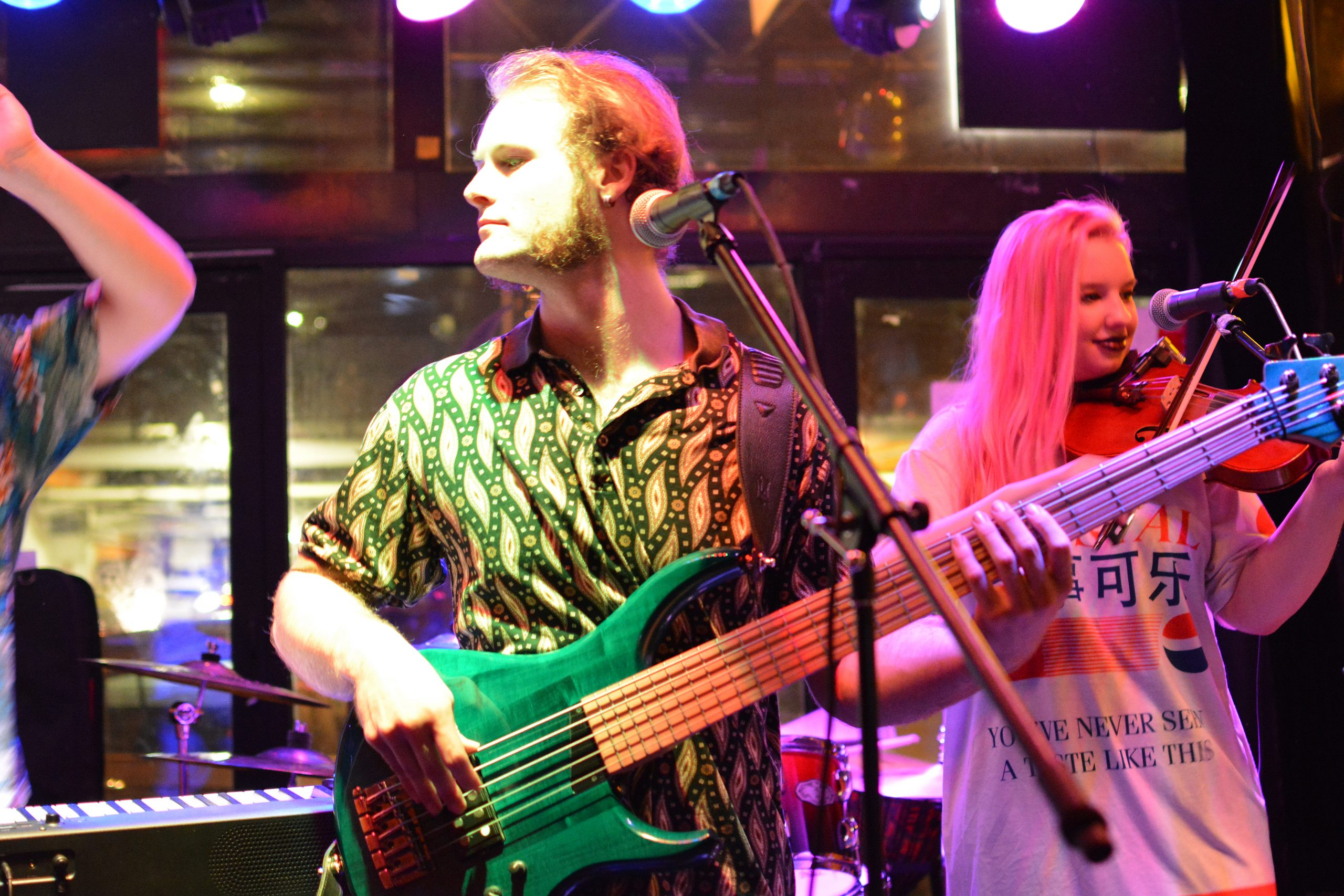 Saul plays the bass guitar; Emma plays the fiddle in the background on the right side of the image